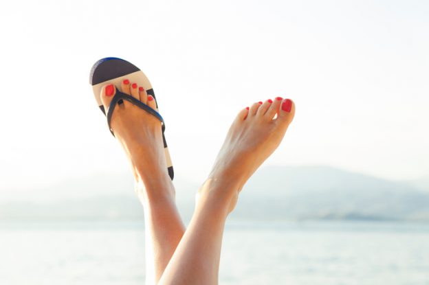 A woman, wearing one black and white sandal, crossing her feet together high up in the air.