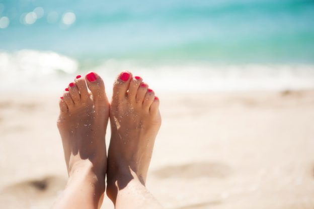 A woman holding up her sand-covered feet up with the ocean in the background.