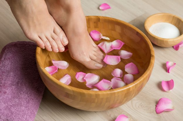 Closeup shot of a woman feet dipped in water with petals in a wooden bowl. Beautiful female feet at spa salon on pedicure procedure. Shallow depth of field with focus on feet. Baby foot Peel