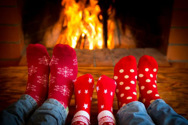 a family has their feet near the fire, keeping them warm and heathy with baby foot products