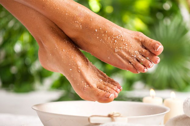 A woman gets an exfoliating sugar scrub applied to her feet.