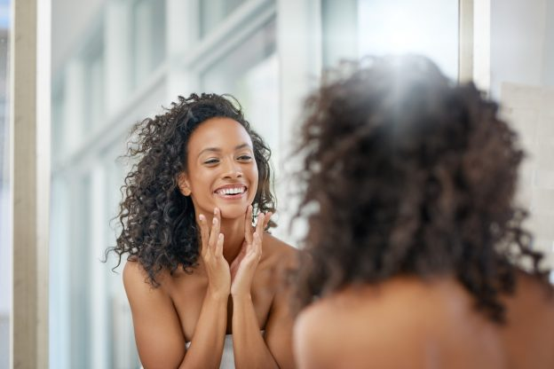 A woman wearing a towel around her torso, smiling while looking at herself in the mirror.